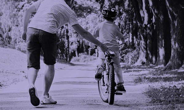 Man helping child to cycle