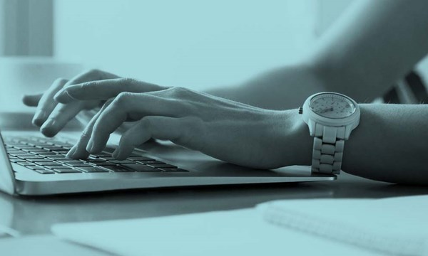 Woman's hands typing on laptop at workplace