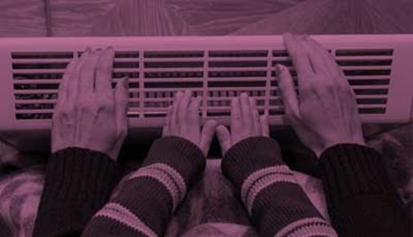 Mother and son heating up a hands in front of an electric heater