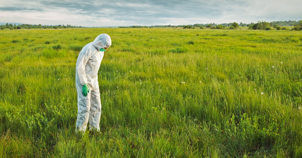 Hazmat guy in a green field