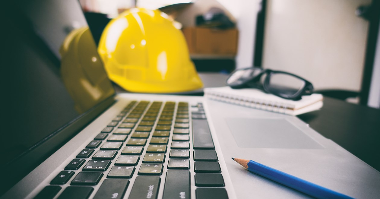 Hard hat, laptop and pencil on desk