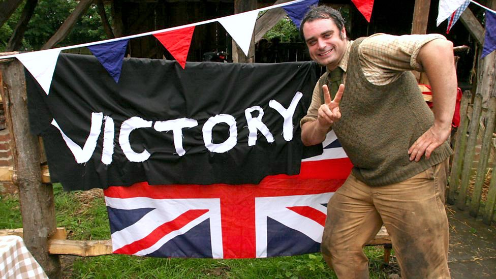 Peter Ginn poses with bunting in a garden
