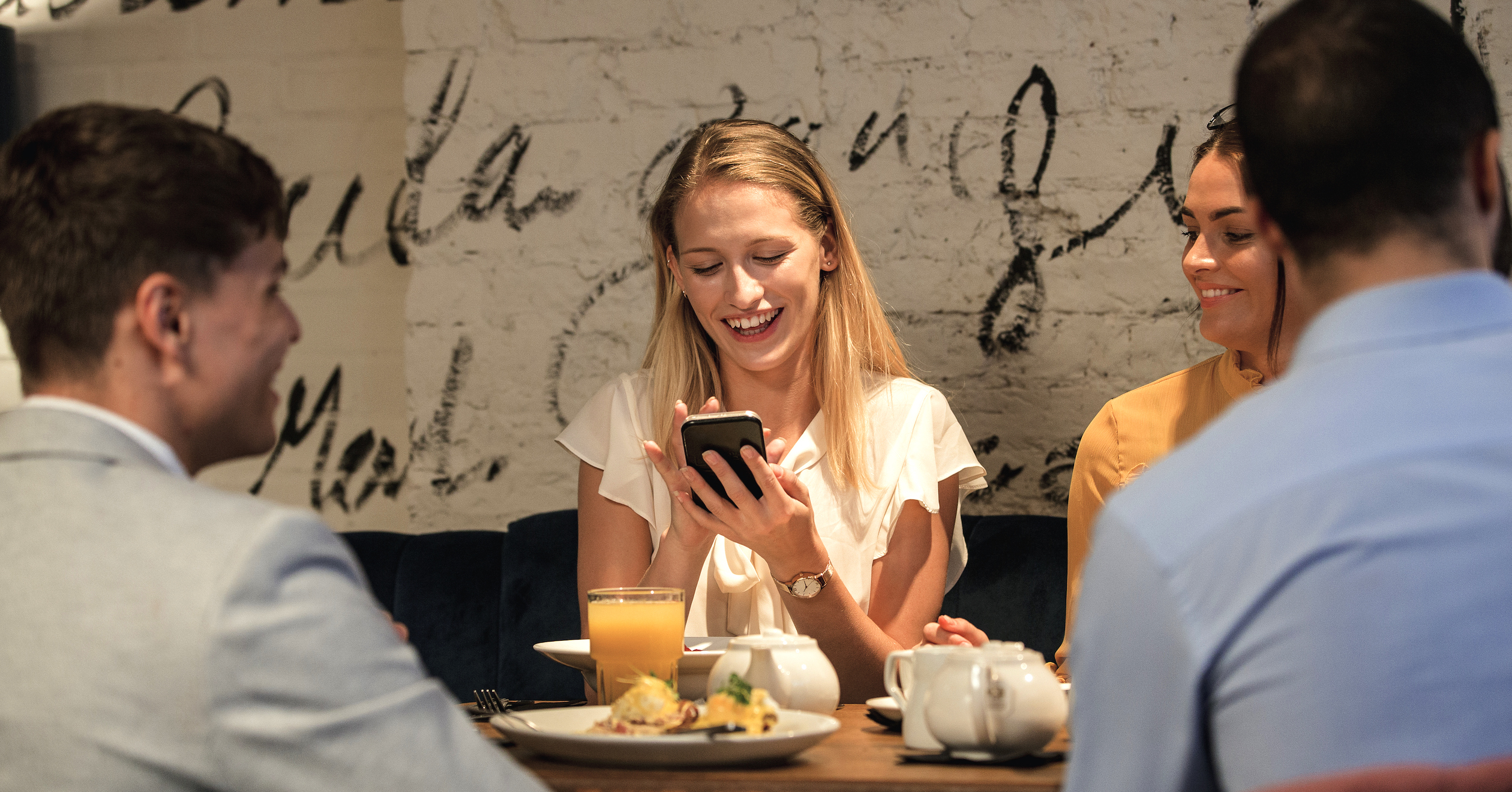Women using phone at dinner with friends