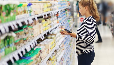 Woman reading ingredients label in supermarket