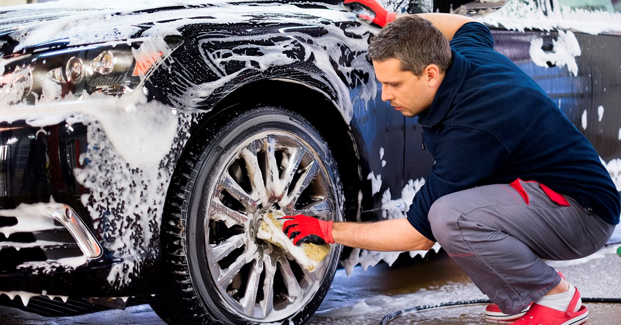 A man washing a car's front wheel