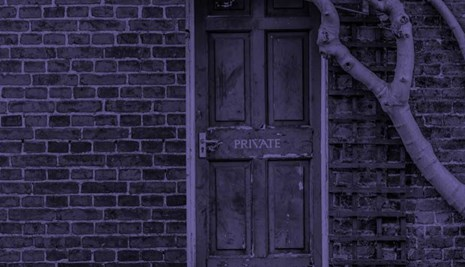 Brick building with a door marked private