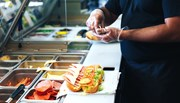 A man handling food behind a sandwich counter with plastic gloves