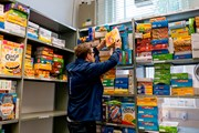 A person stacking shelves at a food bank