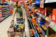 Woman pushes trolley in supermarket