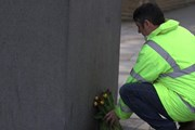 A protester placing flowers at the 'Unknown construction worker' statue in London