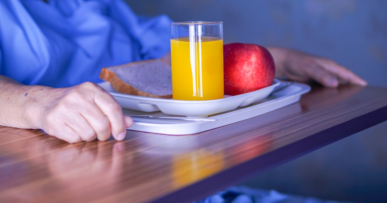 Hospital patient with orange juice and an apple