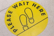 'Wait here' sign on the floor of a shop.