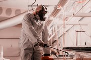 A person in protective clothing spraying a workplace with disinfectant