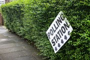 UK polling station sign, wonky against a green hedge
