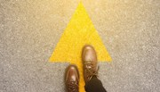 Brown shoes facing forward on top of a yellow arrow