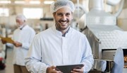 Male factory worker wearing white coat and hair net smiling